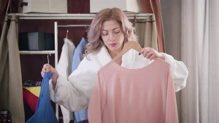 Portrait of young confident girl trying on blue shirt and pink blouse. Beautiful woman in white bathrobe choosing elegant outfit in the morning. Style, fashion.