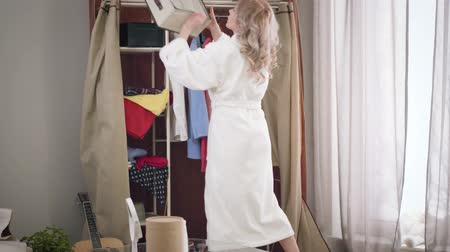 Back view of elegant Caucasian girl in white bathrobe searching something in wardrobe. Worried woman looking at shelves from up to down. Fashion, style.