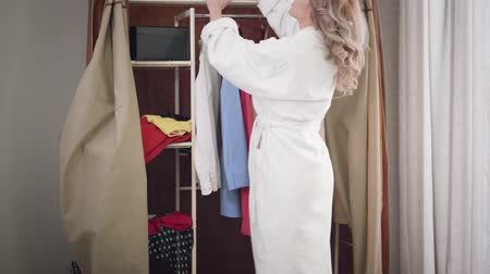 seçme : Camera following young Caucasian girl searching for dress in wardrobe. Nervous woman in white bathrobe looking for outfit at shelves. Style, fashion. Stok Video