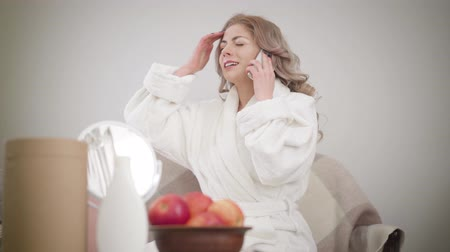 Portrait of cheerful Caucasian girl in white bathrobe sitting on couch and talking on the phone. Beautiful woman gesturing emotionally. Happiness, lifestyle, leisure.