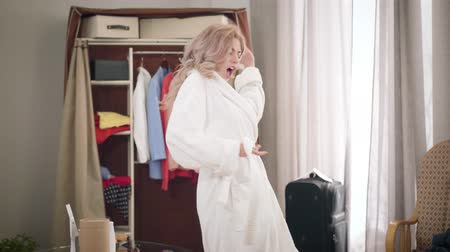 Portrait of young beautiful Caucasian woman dancing and singing at home. Cheerful girl in white bathrobe enjoying sunny morning indoors. Joy, lifestyle, happiness. 影像素材