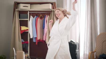 Energetic dance of young beautiful woman at home. Pretty girl in white bathrobe spinning as enjoying weekends indoors. Happiness, lifestyle, joy.