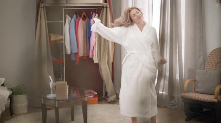 excitação : Young Caucasian woman in white bathrobe dancing and gesturing at home. Happy female melomaniac enjoying music on weekends. Hobby, lifestyle, happiness.