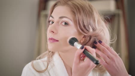 щеткой : Close-up face of confident Caucasian girl applying face powder and fixing eyebrows. Smiling young woman getting ready in the morning. Fashion, beauty, lifestyle.