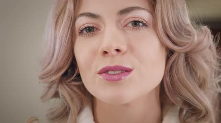 Close-up of charming Caucasian woman applying lipstick, sending air kiss to camera and winking. Happy beautiful girl doing make-up indoors, getting ready for date. Beauty, lifestyle.