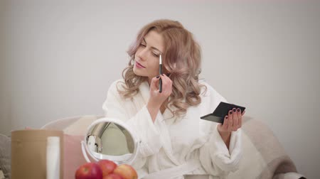 Portrait of young Caucasian woman looking at mirror and applying eye shadows. Charming girl in white bathrobe getting ready in the morning. Cosmetics, make-up, beauty.