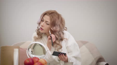 Portrait of attractive Caucasian girl with curly hair applying face blushes. Young lady in white bathrobe doing make-up. Lifestyle, beauty.