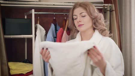 Young Caucasian woman taking white towel from wardrobe and smelling it. Smiling girl enjoying freshness of clean laundry at home. Household, cleanliness, whiteness.