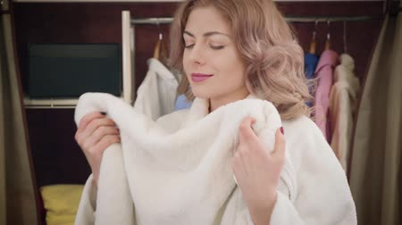 Portrait of satisfied young Caucasian woman in white bathrobe smelling and hugging clean towel. Diligent housewife satisfied with freshness of laundry. Happiness, lifestyle.