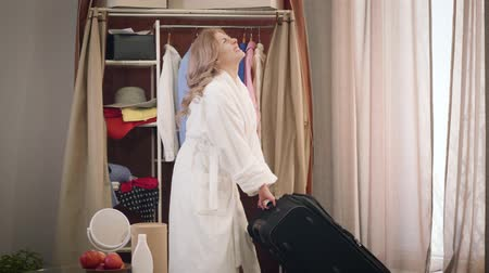 Beautiful Caucasian girl in white bathrobe dragging heavy travel bag. Charming woman packing for a trip. Travelling, lifestyle, tourism.