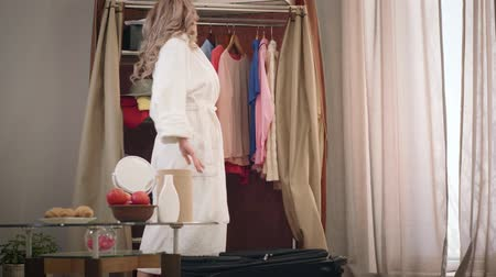 motivasyonel : Exhausted Caucasian girl signing and sitting down next to suitcase. Young tired woman in white bathrobe packing clothes before the trip. Travelling, tourism, lifestyle. Stok Video