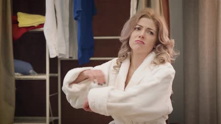 Close-up of upset Caucasian woman taking off hat and putting head on hands. Beautiful sad girl in white bathrobe sitting indoors. Problems, depression. Stok Video