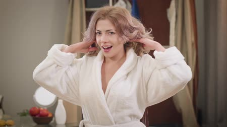 Portrait of charming young woman in white bathrobe posing at home. Caucasian girl fixing curly hair and looking at camera. Beauty, style, happiness.