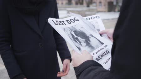 kutya : Close-up of male Caucasian hands giving missing dog ad to unrecognizable woman. People searching for their lost pet on streets. Despair, loss. Stock mozgókép