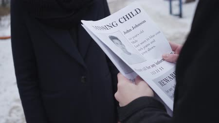 broşür : Young Caucasian man giving missing child ad to unrecognizable woman on the street. Father searching for his kidnapped son. Loss, depression, despair.