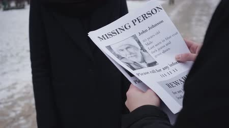 broşür : Close-up of missing person ad given by unrecognizable man to young Caucasian woman on the street. Son searching for his lost mature father. Despair, loss, social issues.