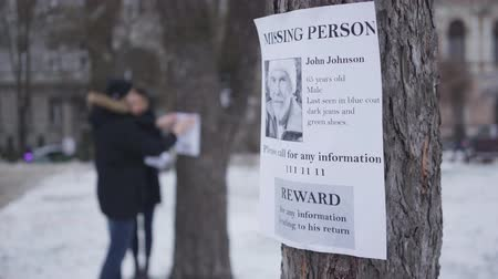 Close-up of missing person ad with information about lost senior Caucasian man. Blurred people hanging ads on trees at the background. Family searching for their grandfather. Unity, loss, kidnapping.