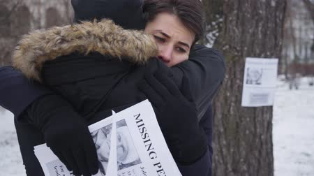 отчаянный : Unrecognizable young man hugging desperate Caucasian woman holding missing person ads. Beautiful brunette girl with brown eyes searching for her lost father. Depression, despair, loss. Стоковые видеозаписи