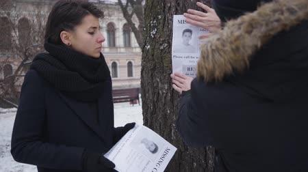 broşür : Caucasian man hanging missing son ad on the tree as his upset wife standing with other booklets. People leaving the shot. Kidnapping, loss, despair. Stok Video