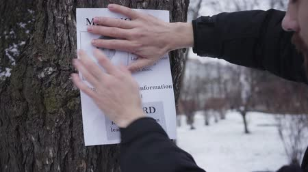 brochura : Bearded Caucasian man hanging missing boy ad on the tree. Young father searching for his lost son. Kidnapping, despair, social problems.