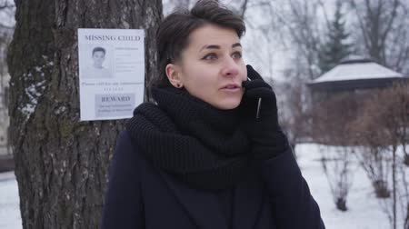 broşür : Portrait of excited Caucasian young woman calling on the phone and looking back at missing child ad hanging on the tree. Empathic girl helping people to find lost person. Kidnapping, loss, search.