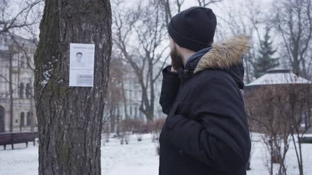 Young bearded Caucasian man talking on the phone and looking at missing person ad hanging on the tree. Empathic guy in winter clothes helping people to find lost person. Kidnapping, loss, search.