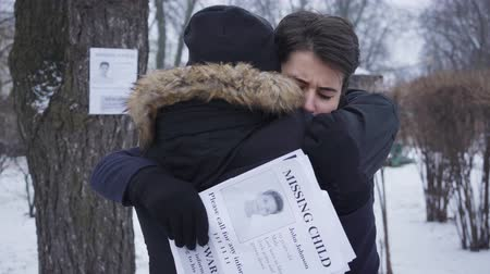 broşür : Back view of man in winter clothes hugging desperate young Caucasian woman. Mother holding ads with information about her lost son. Kidnapping, searching.
