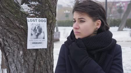Close-up portrait of sad Caucasian girl standing on winter street and looking around. Announcement about lost dog hanging on the tree at the background. Loss, problem, despair.