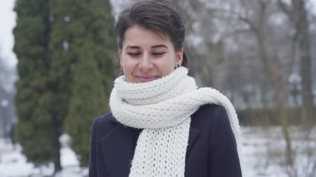 poco : Camera zooming out little from face of charming Caucasian girl in white scarf standing outdoors. Portrait of beautiful young woman looking at camera and smiling. Filmati Stock
