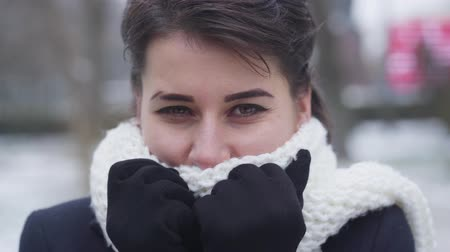 Close-up of young brunette Caucasian girl with brown eyes hiding face in white warm scarf. Portrait of cute woman looking at camera as standing on winter street. Leisure, beauty.