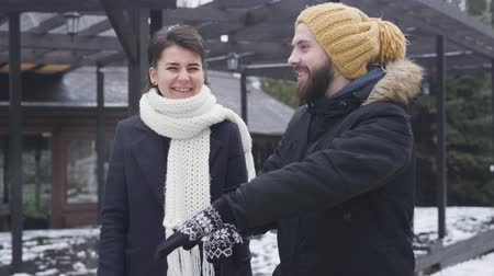 Portrait of Caucasian man and woman walking along the street in winter outfit. Cheerful boyfriend and girlfriend or young family enjoying strolling outdoors. Happiness, unity, lifestyle.