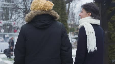 inspirerend : Back view of happy young Caucasian couple strolling along winter street and talking. Bearded guy in yellow hat and charming girl in white scarf dating outdoors. Love, leisure, happiness. Stockvideo