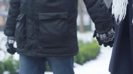 ruhák : Close-up of male and female hands in winter gloves holding each other. Man and woman strolling outdoors. Leisure, lifestyle.