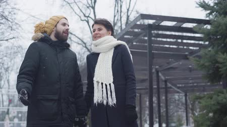 mókás : Middle shot of smiling Caucasian couple strolling outdoors. Man in funny yellow hat and charming woman in white scarf dating in winter. Love, relationship, bonding. Stock mozgókép