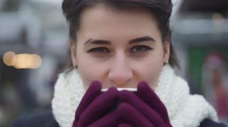 inspirerend : Extreme close-up of brunette Caucasian woman with brown eyes looking at camera and tasting hot coffee. Smiling young girl in white scarf posing outdoors. Lifestyle, happiness, leisure.