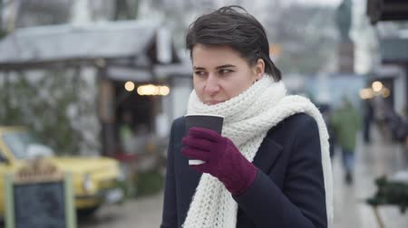 Frozen young Caucasian woman standing at winter fair drinking hot coffee and talking. Beautiful girl in coat and white scarf spending weekends outdoors. Lifestyle, leisure.