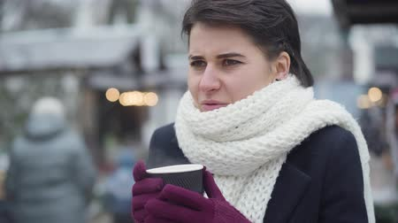 Close-up of beautiful Caucasian woman in white scarf drinking coffee outdoors. Frozen young girl with brown eyes standing on winter fair with a cup of hot drink. Leisure, resting, lifestyle.