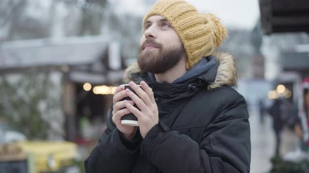 inspirerend : Portrait of young bearded Caucasian man in funny yellow hat and winter coat warming up with hot coffee outdoors. Frozen handsome guy standing at winter fair and smiling. Leisure, lifestyle, happiness.