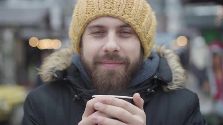 kupa : Close-up portrait of frozen young Caucasian man drinking hot coffee on the street. Cheerful guy in yellow hat and winter coat looking at camera. Leisure, lifestyle. Stok Video