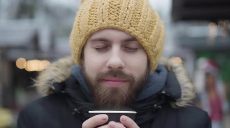 Close-up face of bearded Caucasian guy in yellow hat enjoying hot coffee outdoors. Young handsome man with brown eyes spending free time on winter fair. Lifestyle, happiness, leisure. 影像素材