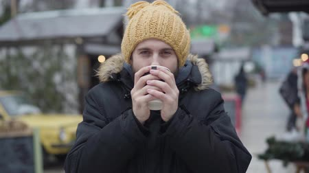 Portrait of adult Caucasian guy with brown eyes standing on winter fair and drinking coffee. Young smiling guy in yellow hat and coat spending weekends outdoors. Leisure, lifestyle.