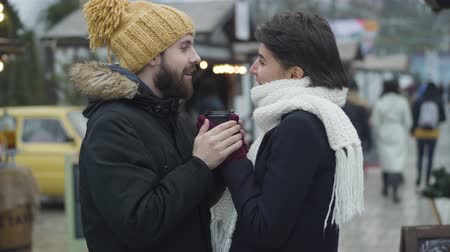 Side view of man and woman in love standing at winter fair and looking at each other. Bearded boyfriend holding girlfriends hands and talking. Unity, love, lifestyle.