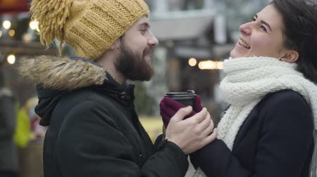 inspirerend : Side view portrait of cheerful Caucasian man and woman standing with coffee cup on winter fair and laughing. Happy young family resting together outdoors. Leisure, lifestyle, relaxation. Stockvideo