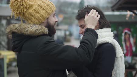 vista lateral : Side view of young Caucasian man in love touching girlfriends hair and talking. Happy couple spending weekends together on winter fair. Happiness, dating, lifestyle.