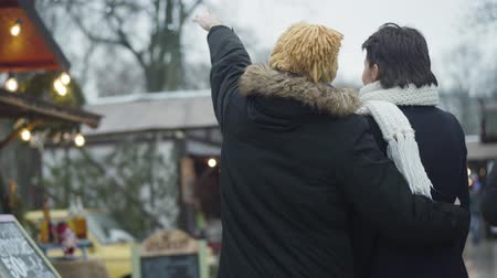 adil : Back view of happy Caucasian couple standing on winter fair and talking. Young man showing something away, woman laughing. Cheerful spouses resting together outdoors. Lifestyle, unity, leisure. Stok Video
