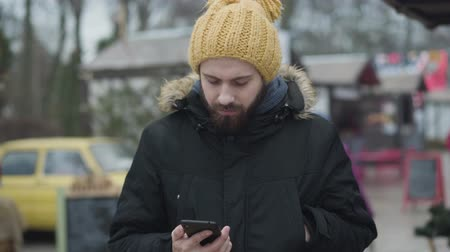 Young frozen Caucasian man standing outdoors dressed in warm clothes and checking time on smartphone. Bearded guy waiting for girlfriend or wife. Lifestyle, relationship, family.