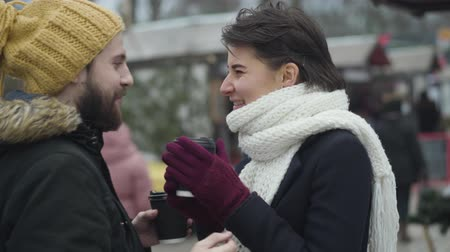Young Caucasian man running up from the background to his girlfriend holding coffee cups. Happy beautiful woman hugging her boyfriend. Cheerful couple warming up with hot drink outdoors. Love, dating.