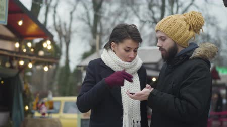 Irritated Caucasian woman talking with bearded husband or boyfriend on the street. Young couple disagree on the place to have dinner. Relationship problems, misunderstanding.