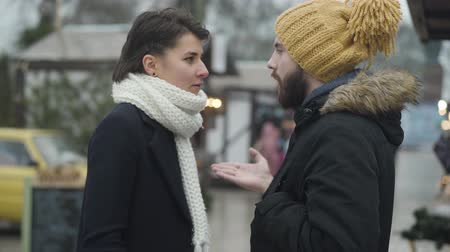 Side view of young Caucasian family arguing outdoors. Beautiful brunette woman and bearded handsome man talking and gesturing emotionally as standing on winter street. Communication problems. 影像素材