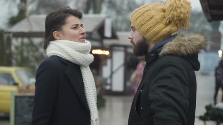 dialog : Portrait of nervous Caucasian woman yelling and gesturing emotionally. Young girl arguing with her boyfriend or husband outdoors. Crisis, conflict, communication problems.